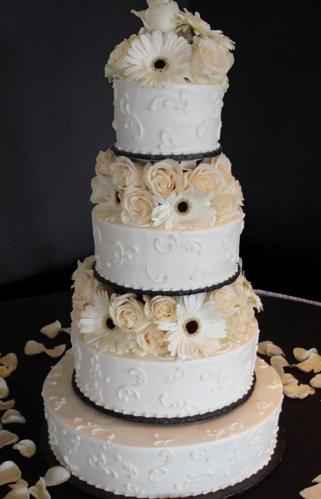 white buttercream iced, 4 tier round wedding cake decorated with a