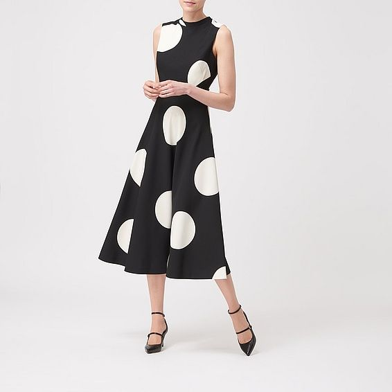 Combining a romantic silhouette with an ultra-modern print, Marlin is a lesson in chic contrasts. This calf-skimming dress features an oversized polka-dot print, a nipped-in waist and a full skirt. Add in monochrome accessories for the sharpest finish.