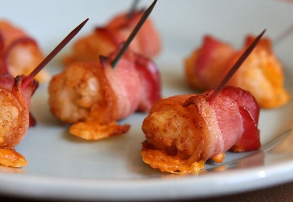 BACON WRAPPED TATER TOTS -- 24 tater tots  12 strips bacon  24 (1/2-inch) chunks sharp cheddar cheese  24 drops Tabasco sauce