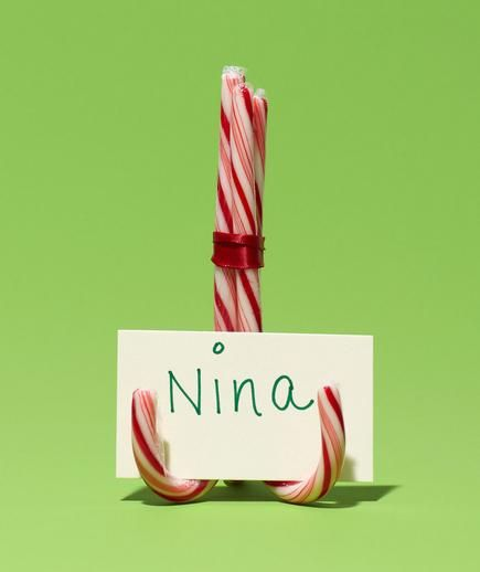 Candy Canes as Place Card Holder -  Perfect for holding a place card. Tie together three canes with a ribbon to make a sturdy stand.