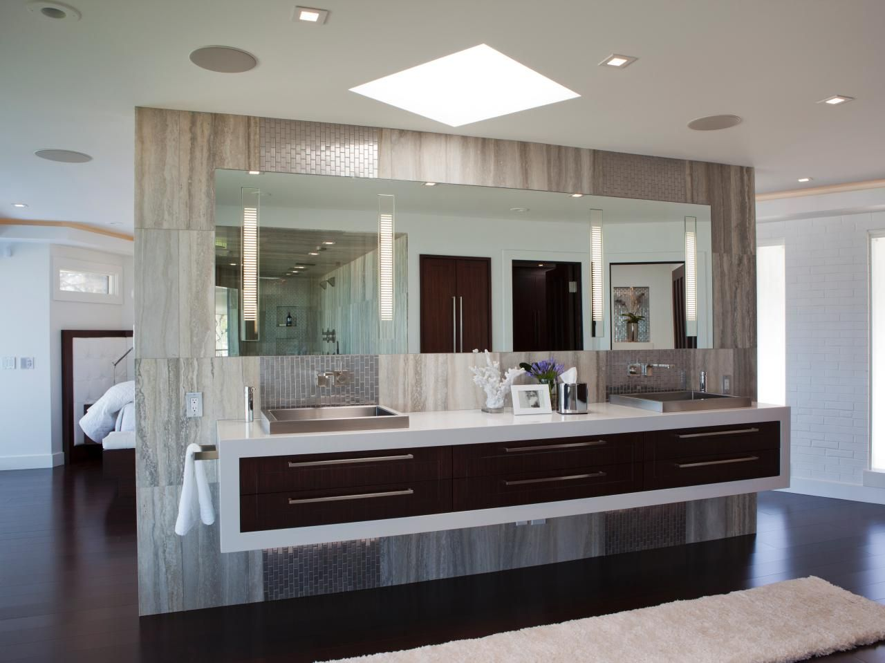 Web Image Gallery This open layout bedroom features a fabulous master bathroom with a floating double vanity Gray tile and chrome fixtures give the space a sleek