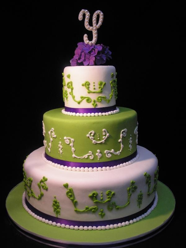 Three Tier Green And Whit Scroll Wedding Cake With Purple Satin