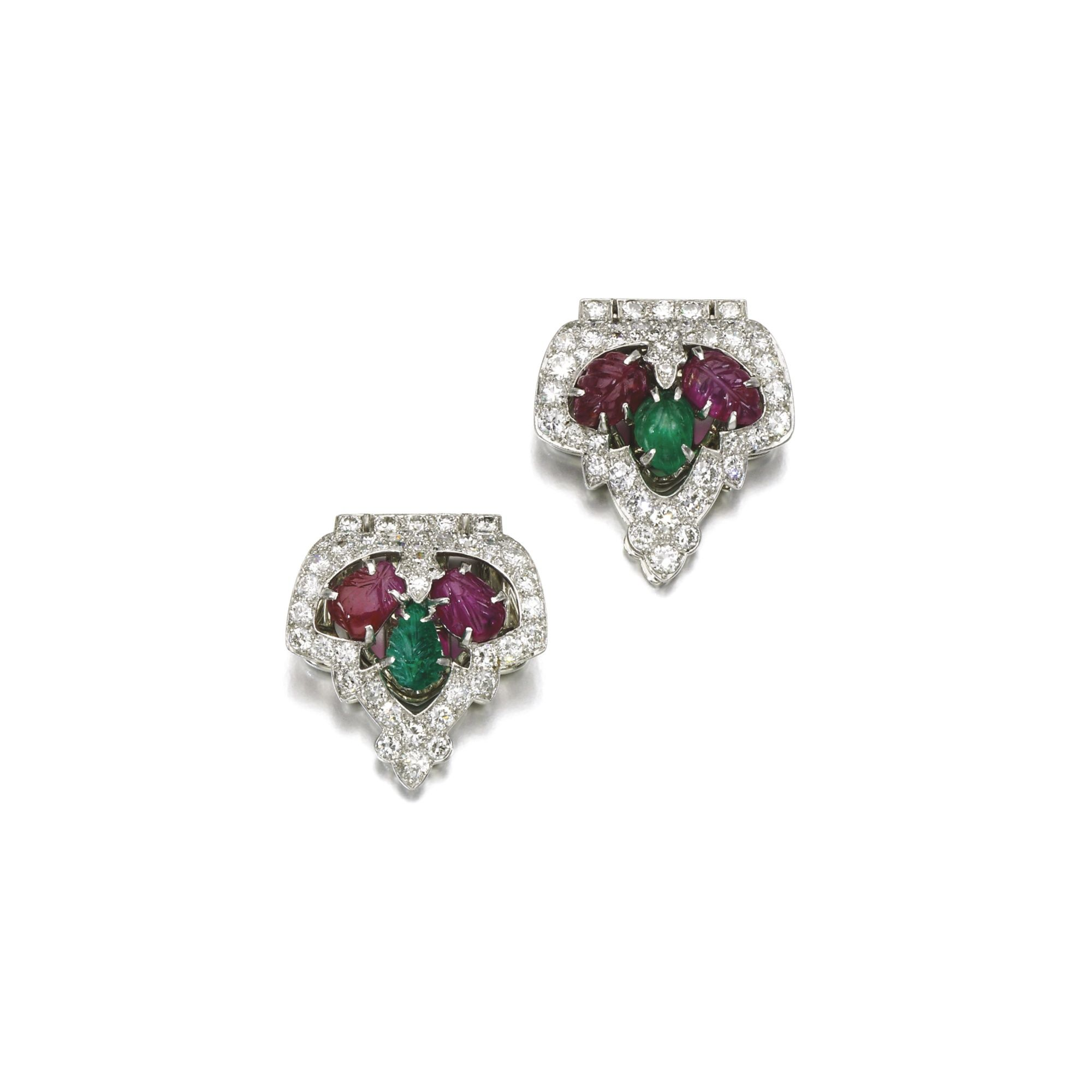 Pair of ruby, emerald and diamond clips, 'Tutti Frutti', Cartier, circa 1925 Each of palmette design, set with a carved emerald and rubies, within a border of circular- and single-cut diamonds, each signed Cartier, one indistinctly numbered.