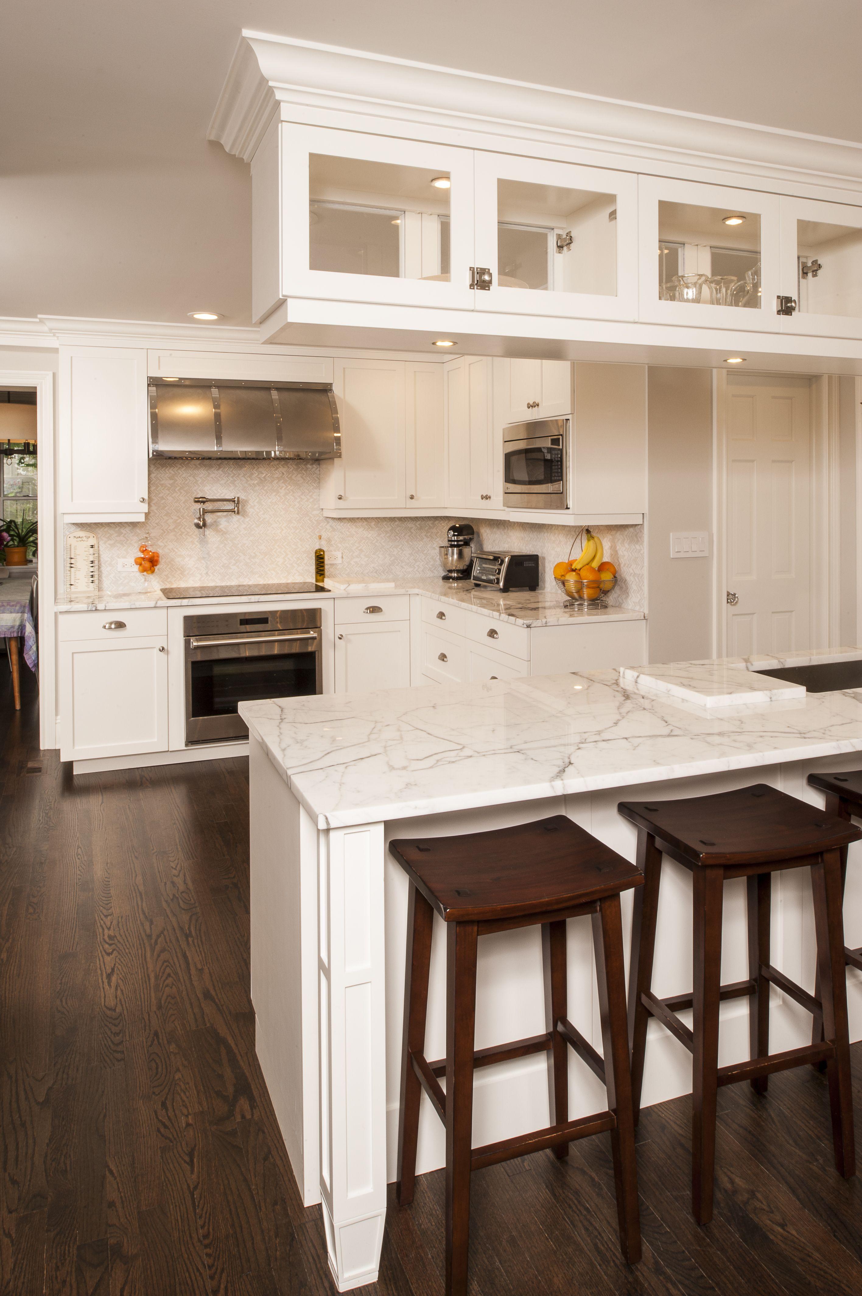 White Kitchen With Peninsula And Glass Display Cabinets Longislandkitchen Longislandluxuryk Classic Kitchens Shaker Style Kitchens Marble Countertops Kitchen White kitchen with peninsula