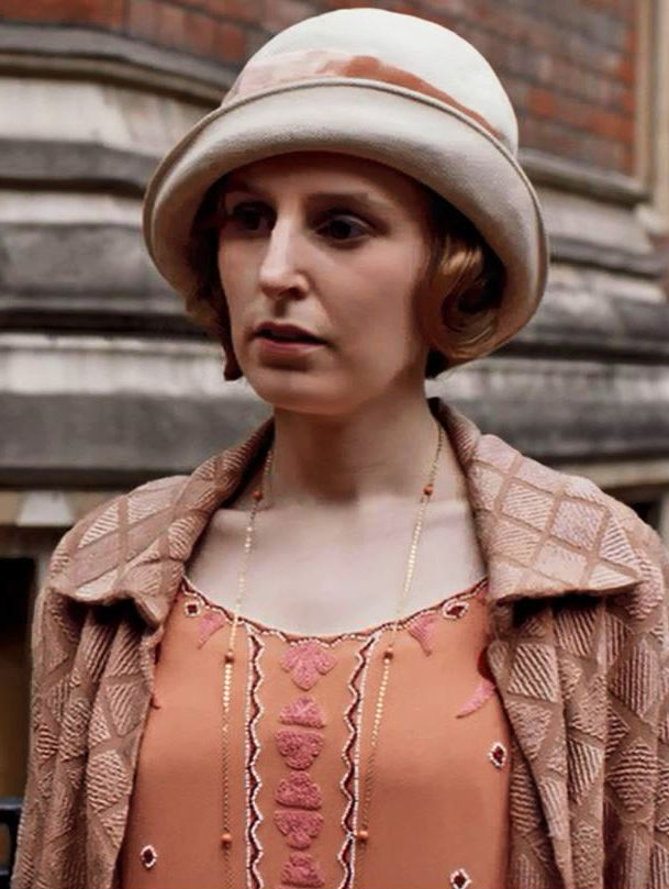 Edith in London wearing a Cloche hat, coral embroidered dress and diamond patterned chenille coat