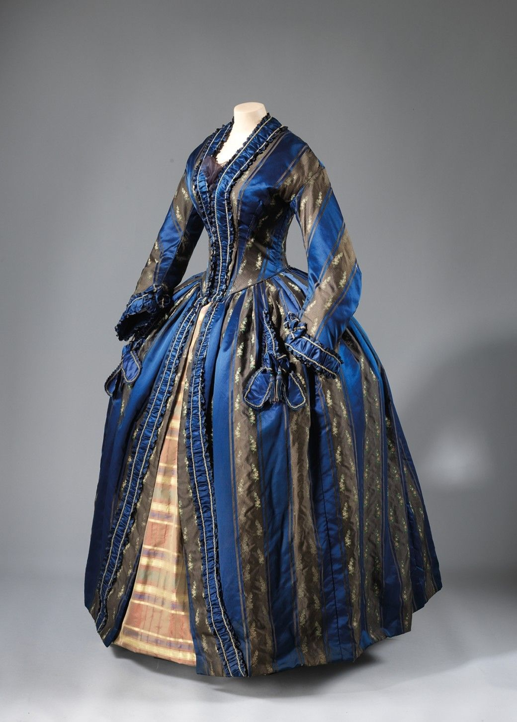 "Deep blue silk and satin striped long-sleeved day dress with quilted silk lining, attributed to the shop of Paris couturière Oudot Manoury. In her 1847 invoice, Mme Manoury described the gown as a ""robe de chambre à la Pompadour,"" the French term for a dressy house coat or dressing gown. The traditional Pompadour form is defined by the open skirt edged with ribbon and the bows on the sleeves and skirt. Unlike the French upper class, American women did not ceremoniously receive guests in…"