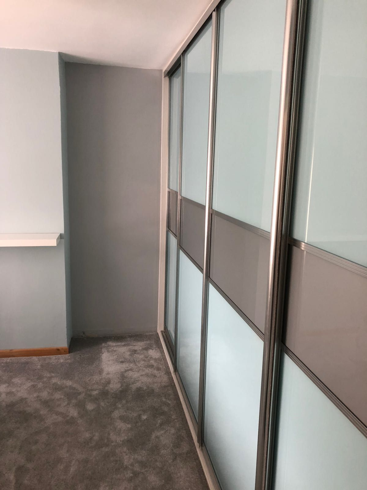 A Large Bedroom Wardrobe With Pale Blue Gl And Grey Middle Band
