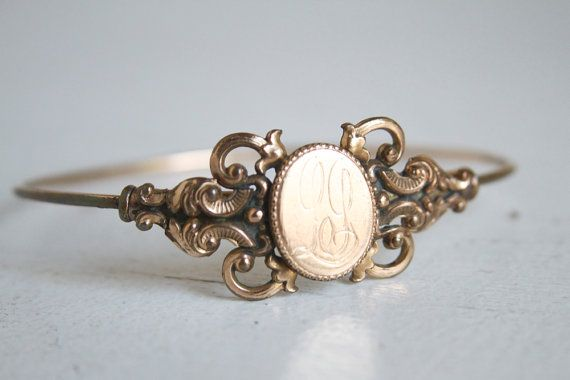 A delicate and ornate Victorian bangle bracelet. The central cartouche has a beautiful monogram. Perfect for the woman who likes her jewels to have their own sense of history.