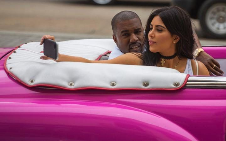 American reality-show star Kim Kardashian takes a selfie as she rides on a classic car next to her husband, rap superstar Kanye West in Havana, Cuba