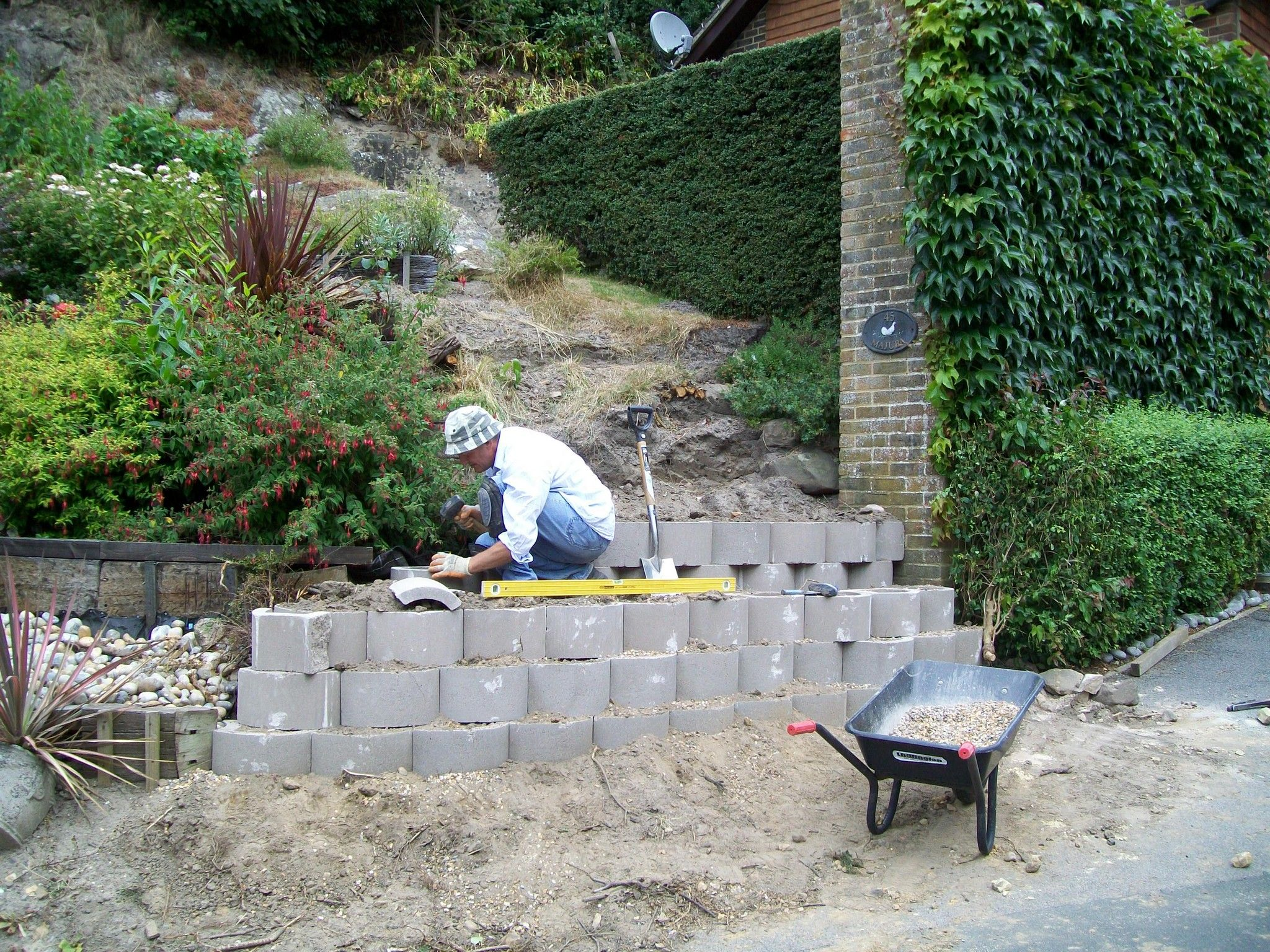 The Beginning Of A Terraced Garden Wall At A Drive Entrance Using The Terraforce L15 Retaining Wall Block Garden Wall Terrace Garden Garden Soil