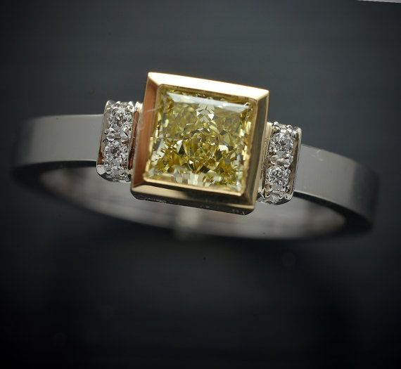 Natural Fancy Intense Yellow VVS diamond GIA certified .69 carats The setting is a Modern Industrial bezel 18kt yellow gold with 8 stones G_VS in micro pave on the shoulders .08ct TW. The band is satin finish in 18kt white gold This is a total custom made ring and can be done with other center stones. All of my jewelry is designed and manufactured at two family owned local manufacturing shops in NYC and my jewelry only uses Conflict Free Diamonds from reputable diamond dealers with Kimberly…