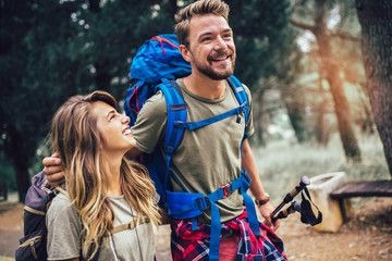 Smiling couple walking with backpacks over natural background
