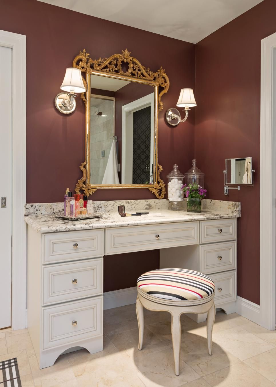 In the corner of this luxe burgundy bathroom, an elegant