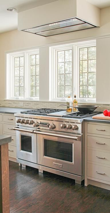 Lovely Kitchen Features Ivory Shaker Cabinets Paired With Pietra Cardosa Limestone Countertops And A White Gray Linear Tiled Backsplash Placed Under