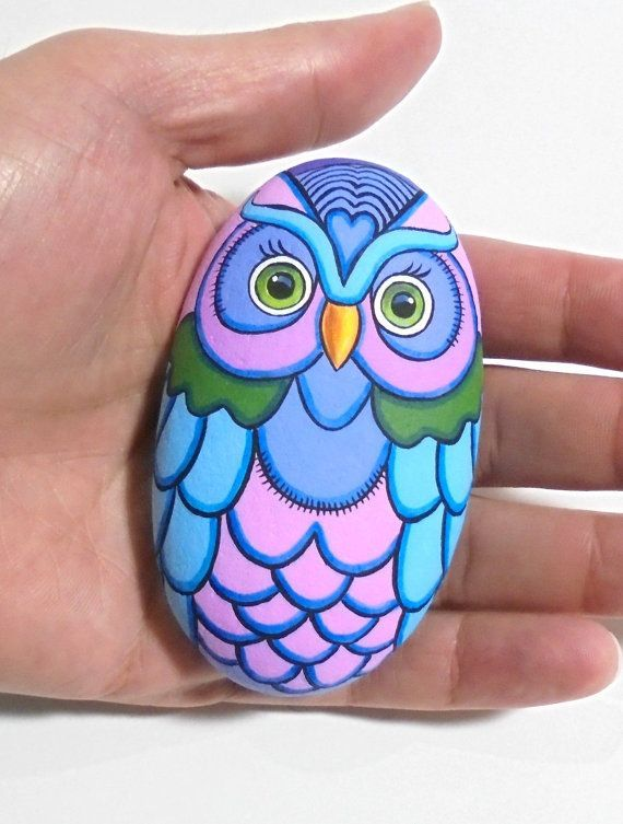 Hand Painted Owl Rock With Modern And Colorful Design! A great hand painted stone made by me!  Is painted on a smooth sea stone which i have collected from a beach on the Greek island of Ikaria. Is painted with fine art quality acrylic colors and very small brushes for the detail , is signed on the back and covert with strong glossy varnish for protection.  Dimensions approximately : Height : 8.5 cm ( 3.3 in ) Width : 4.9 cm ( 1.9 in )  Your art works will arrive carefully packaged. Recommend…