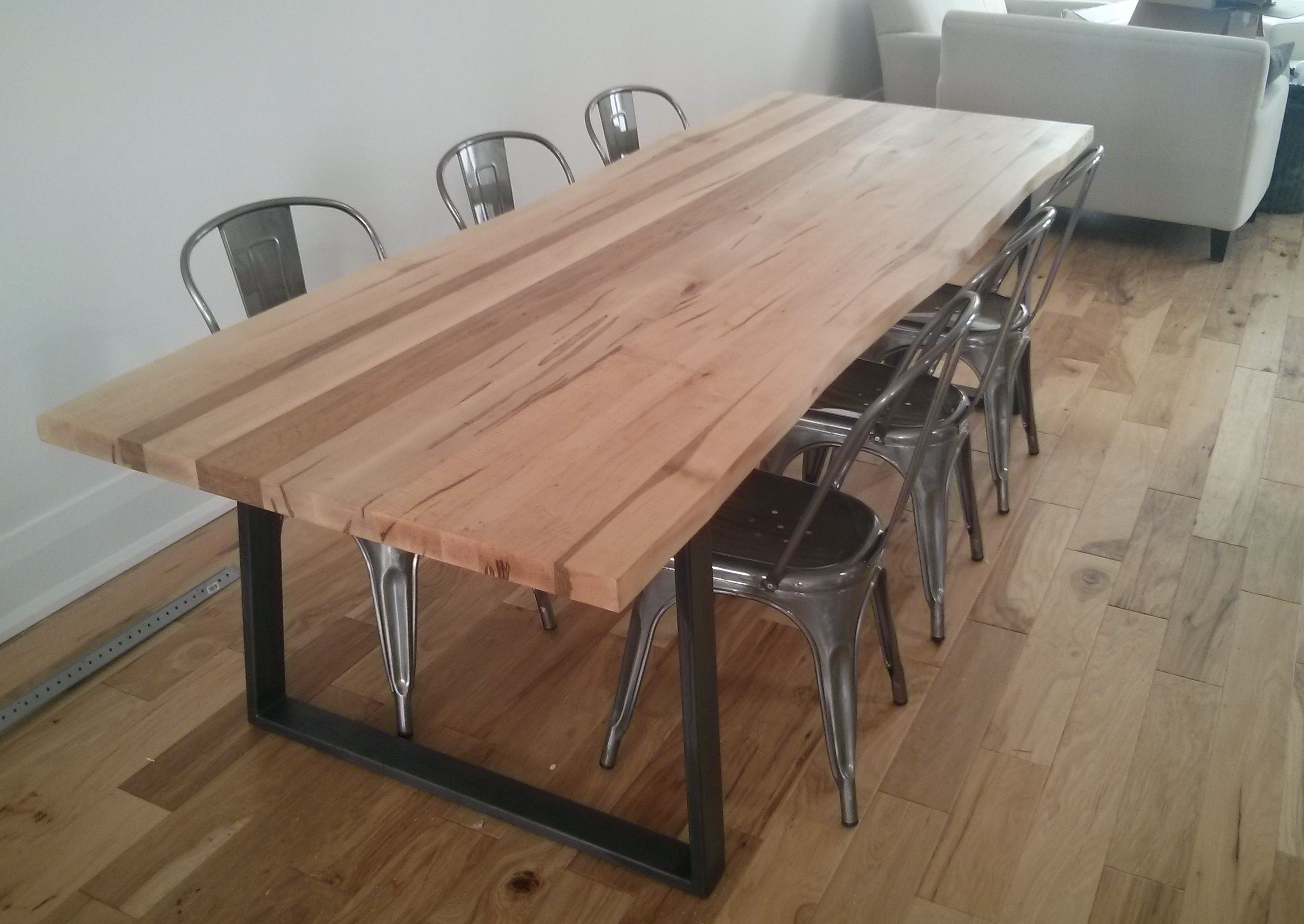 Custom live edge wormy maple dining table with tapered raw steel