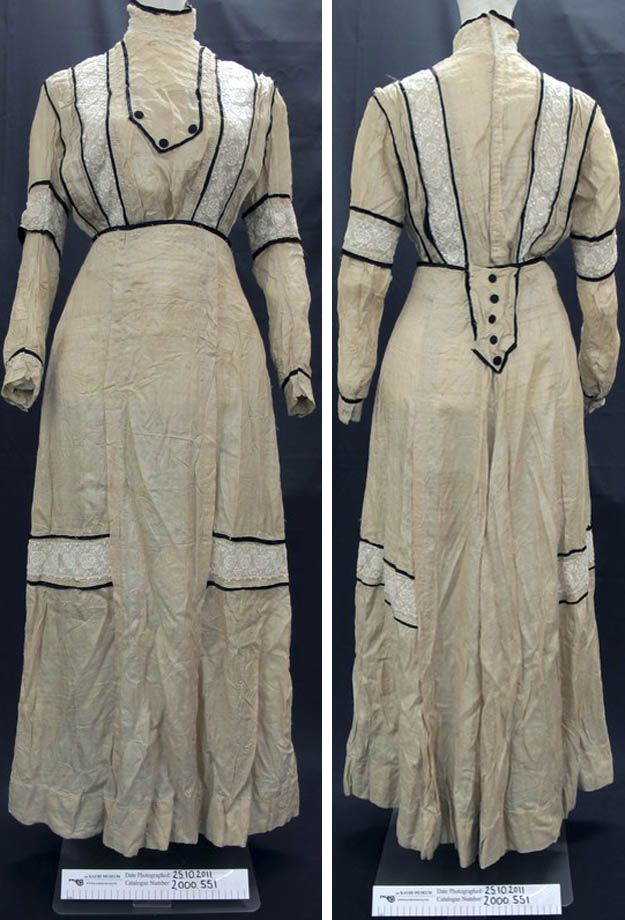 Day dress, circa 1900. Rough cream-colored silk. Blouse has high lace neck w/black binding, lace inserts w/black bias binding at elbows, and 2 vertical stripes on bodice and horizontal band on skirt. Envelope-type decorations at front blouse and back skirt close on waistband w/black-covered button details. Black bias binding at turn-back cuffs, waistband, and neck. Kauri Museum, Matakohe, via NZ Museums.