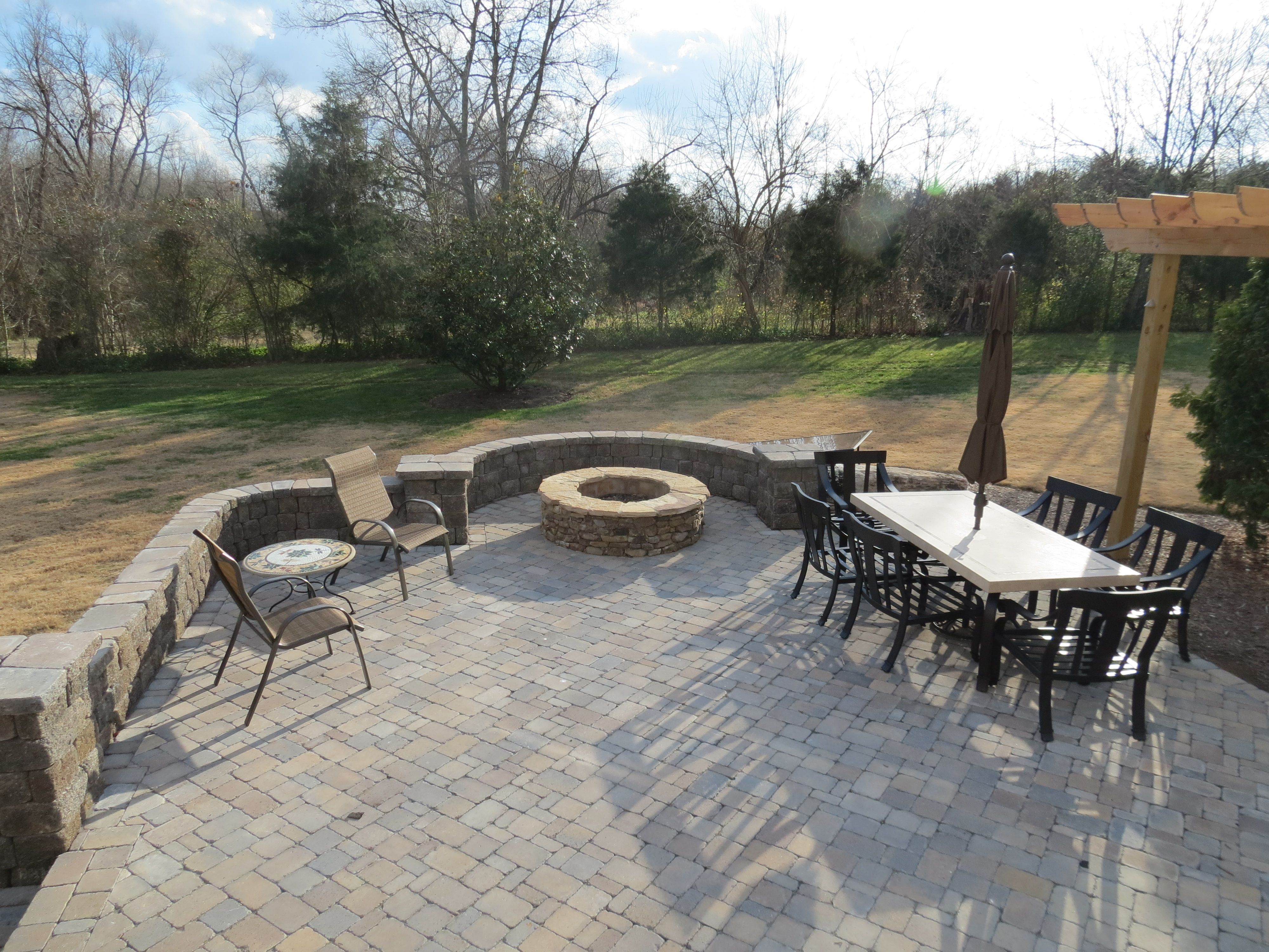 Backyard brick paver patio with natural stone fireplace columns and