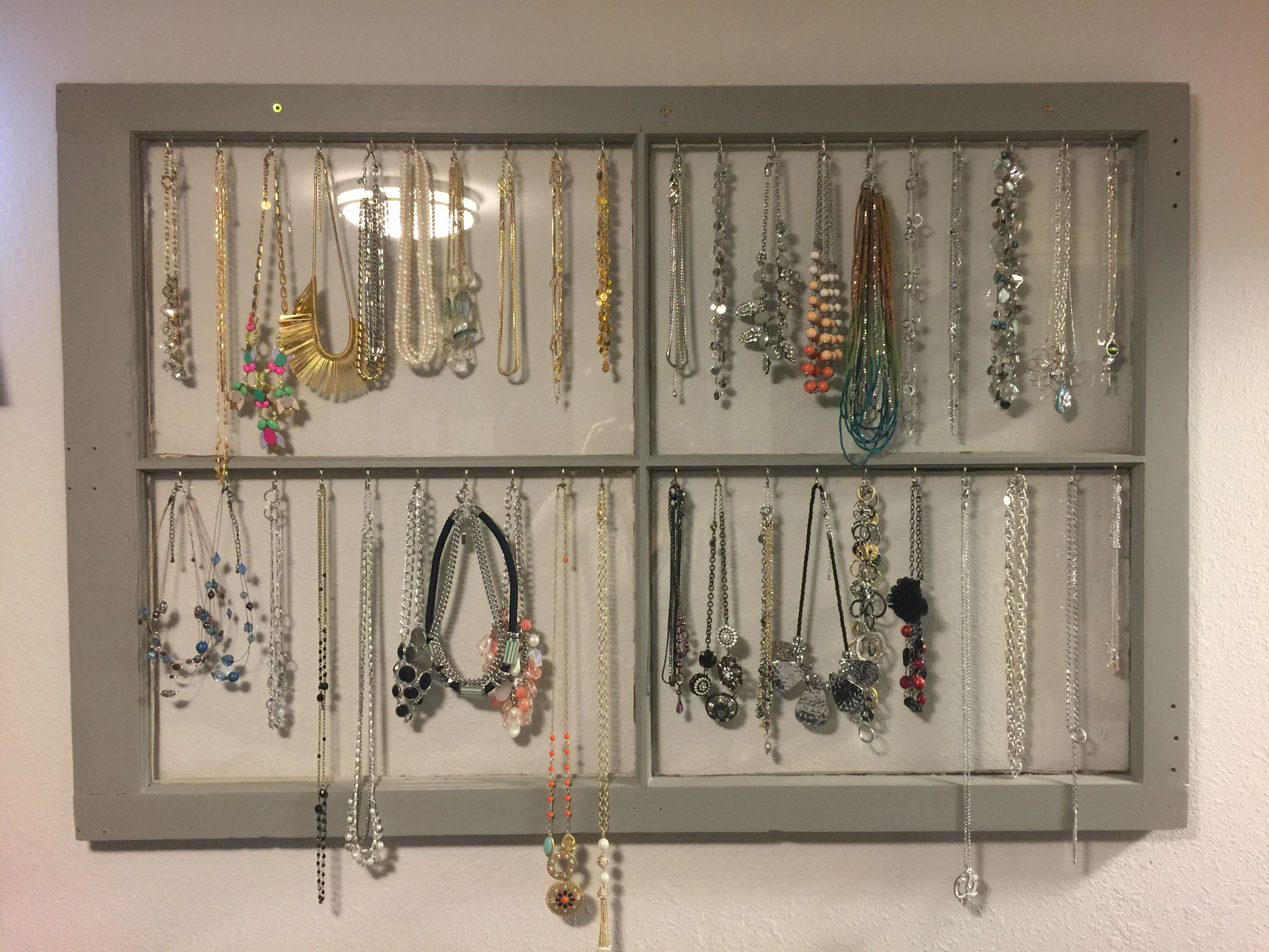 Necklace display/organizer from a $10 window (local re-home store), paint I had from around the house, and 40 cup hooks. Thinking about adding some decorative knobs around the edges for scarves. #diy #necklaceorganizatoon #sopretty #lookslikeadecoration
