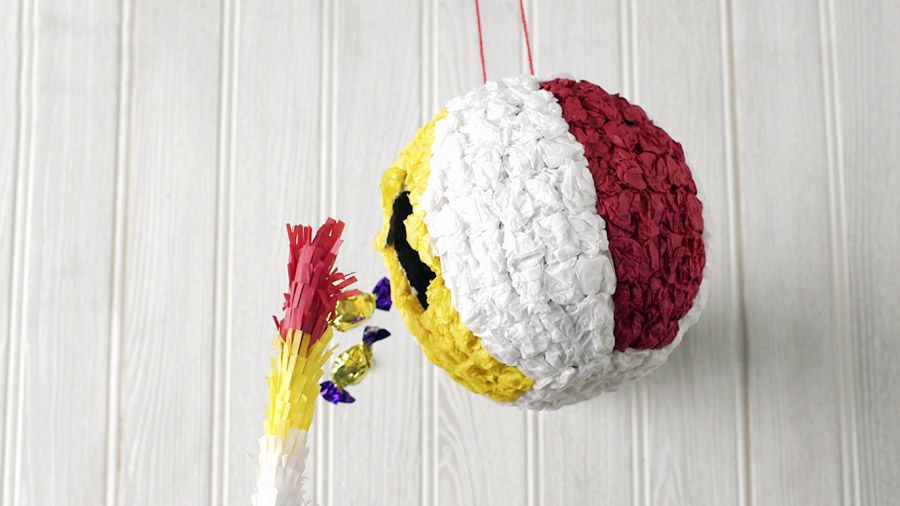 A pinata shaped in a beach ball bursting open with sweets falling out | How to make a beach ball pinata