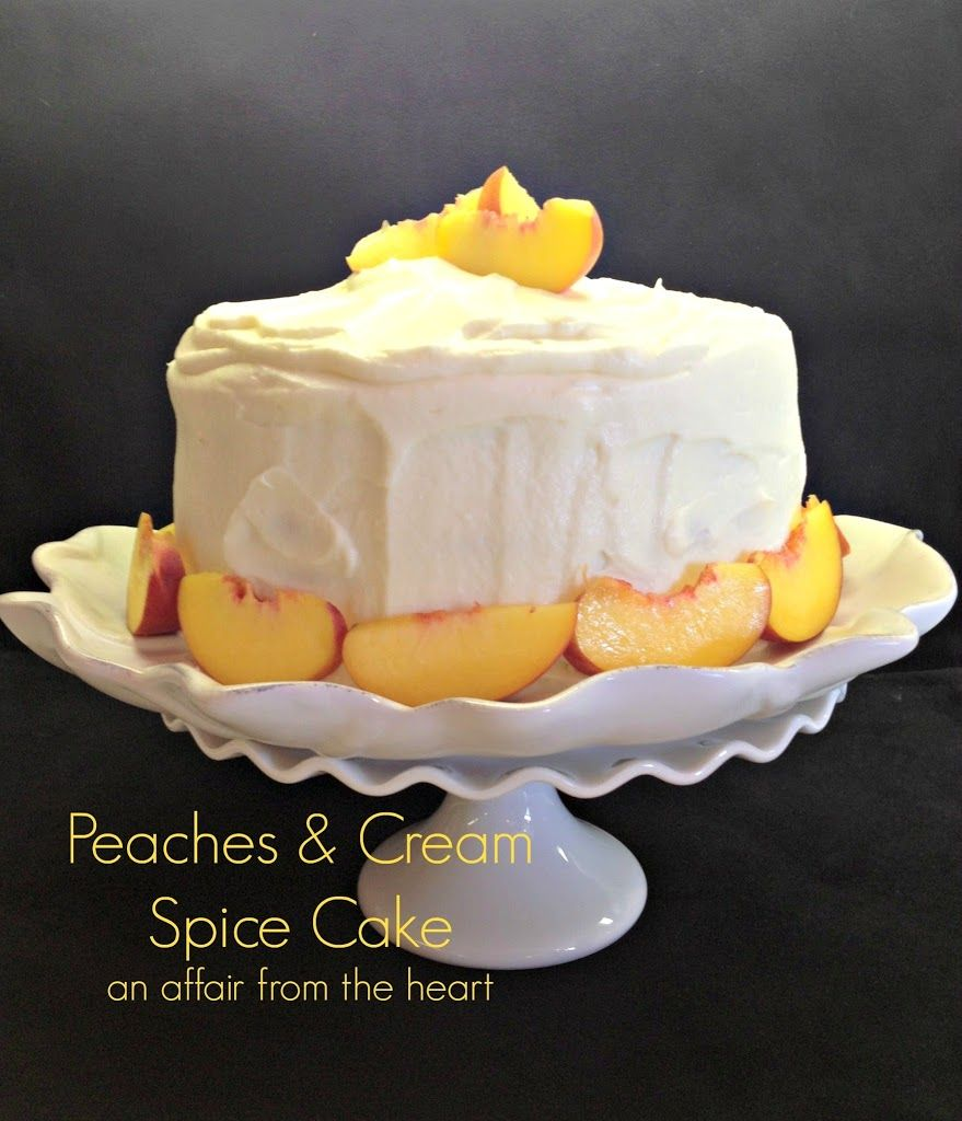 This spice cake has a fresh peach filling and is topped with whipped cream cheese frosting and garnished with more fresh peaches.