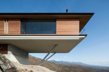 Maison contemporaine en bois en porte à faux sur une colline au