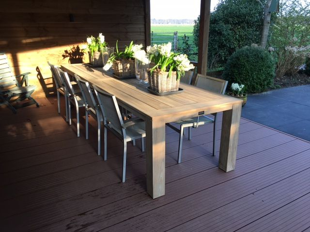 Lange houten tuintafel onder een overkapping buitentafel