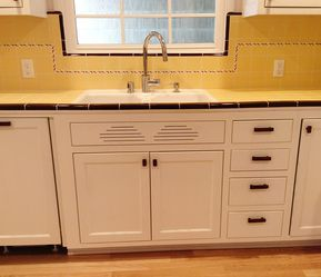 Carolyn's gorgeous 1940s kitchen remodel featuring yellow tile with maroon trim images