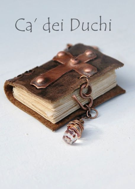 Miniature books.  Looks like a piece of suede with metal work embellishments.