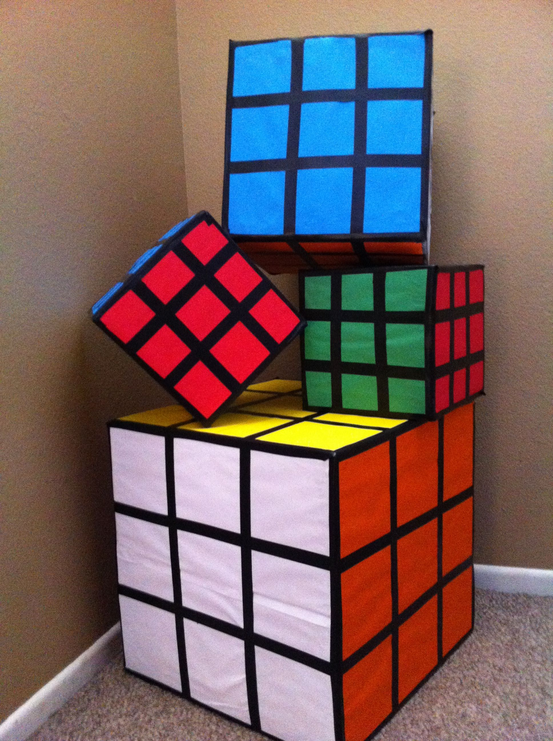 """First time making these Rubix cubes for a 80's party . The mid size one is to hold the  """"gift cards"""" easy and fun to make ! Use various sizes of  square boxes , black electrical tape and color scrapbook paper . I glued all the papers down then used the tape all around. Easy and guest will love how they look!!!"""