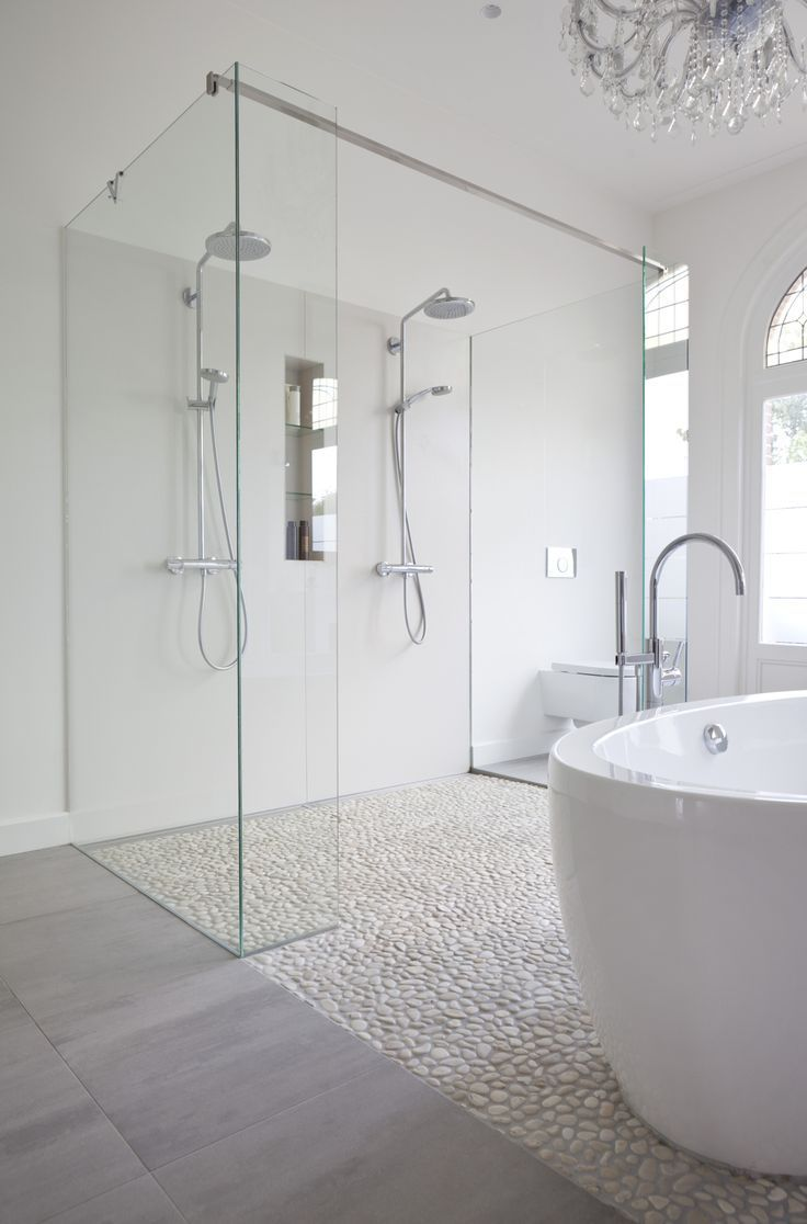 Clean white bathroom using white pebble tile floor in shower and as ...