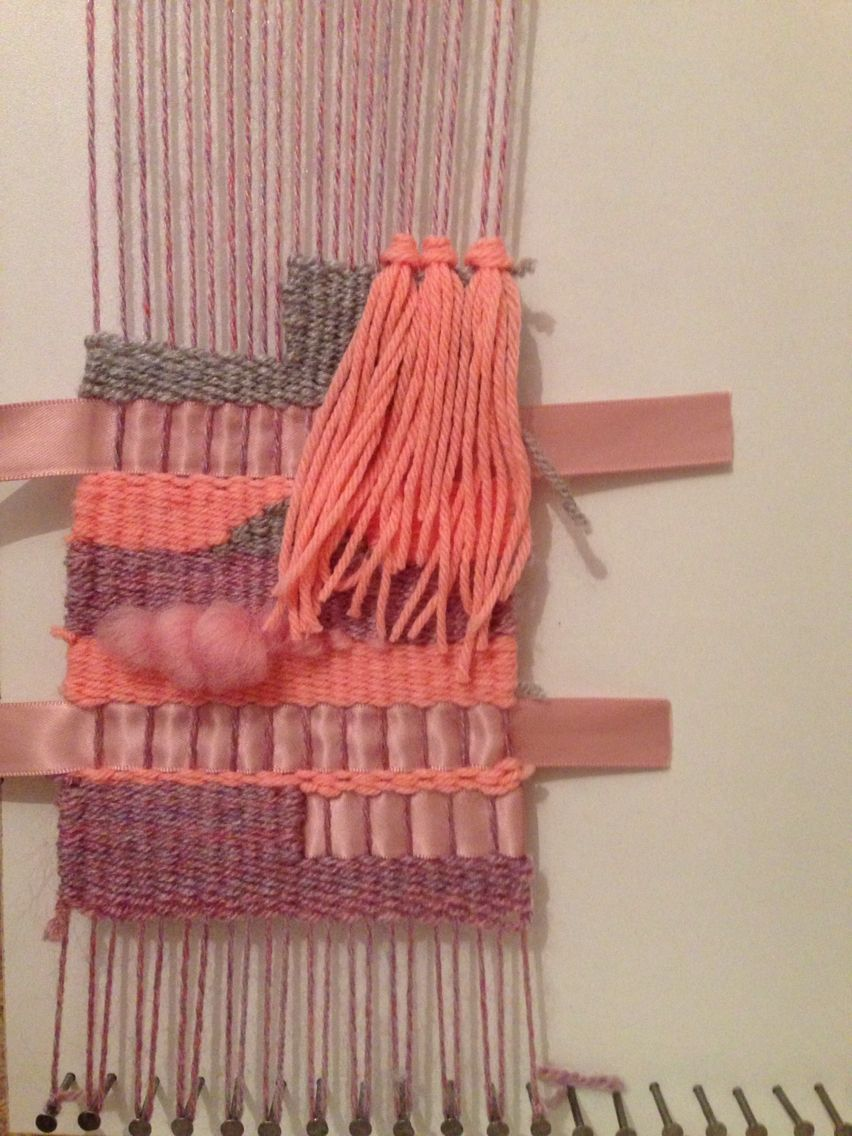 Another weave in the making ! Using pinks grey and purple with scraps of ribbon and wool roving .