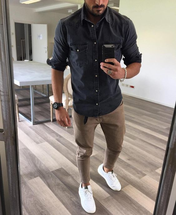 camisa vaquera gris oscuro, pantalón chino marrón, zapatos de lona blancos, reloj negro para hombre