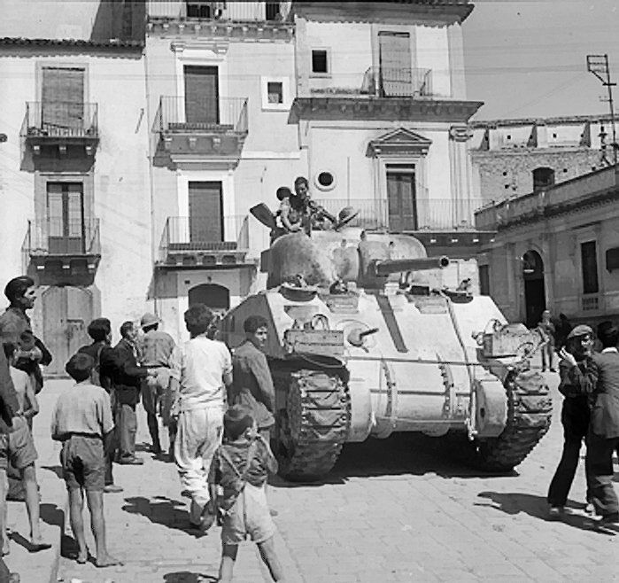 British Sherman tank of XIII Corps, Eighth Army in the streets of Francofonte, Sicily, 13-14 Jul 1943 (Imperial War Museum)