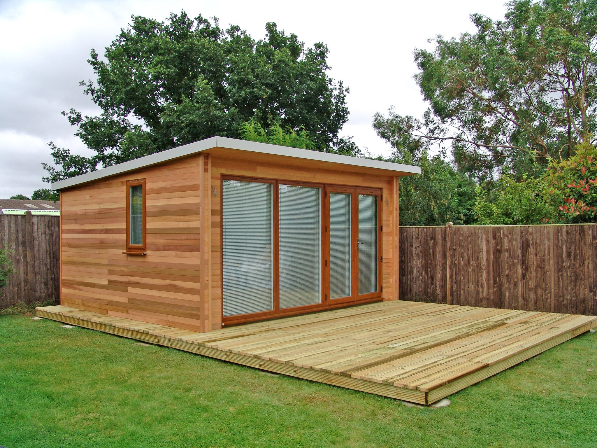 Garden studio with large decking area by garden lodges for Garden area ideas