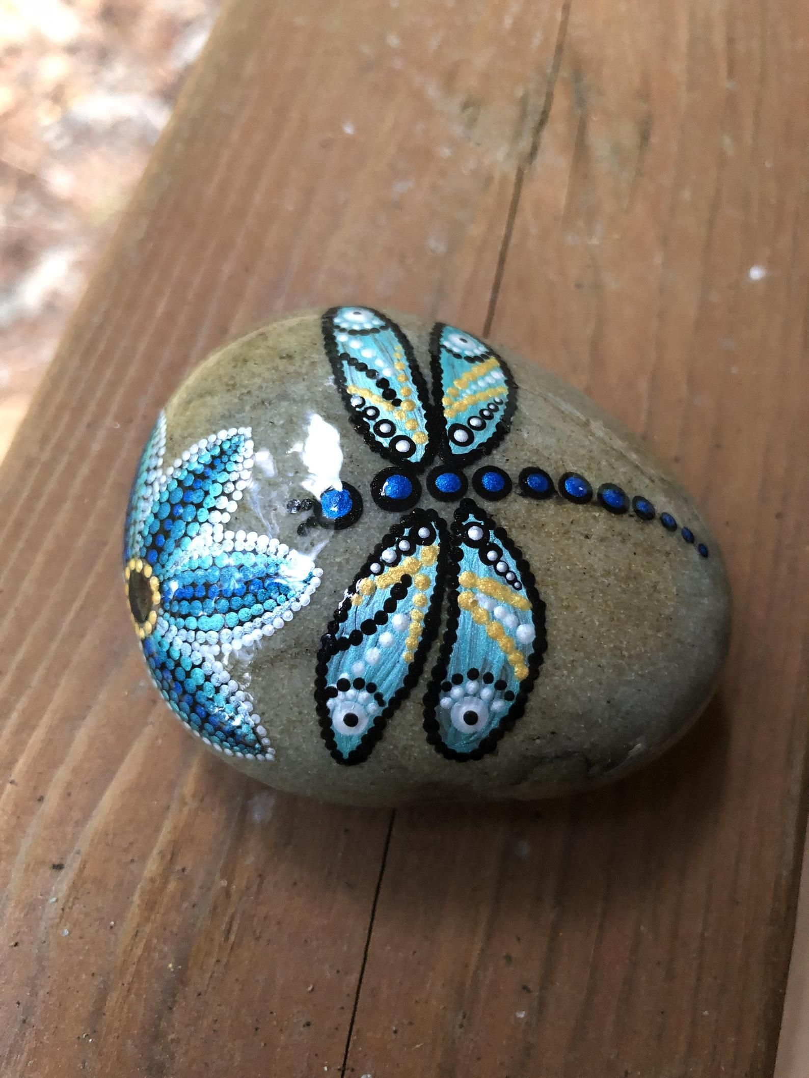 Blue dragonfly and flower dot painted on rock