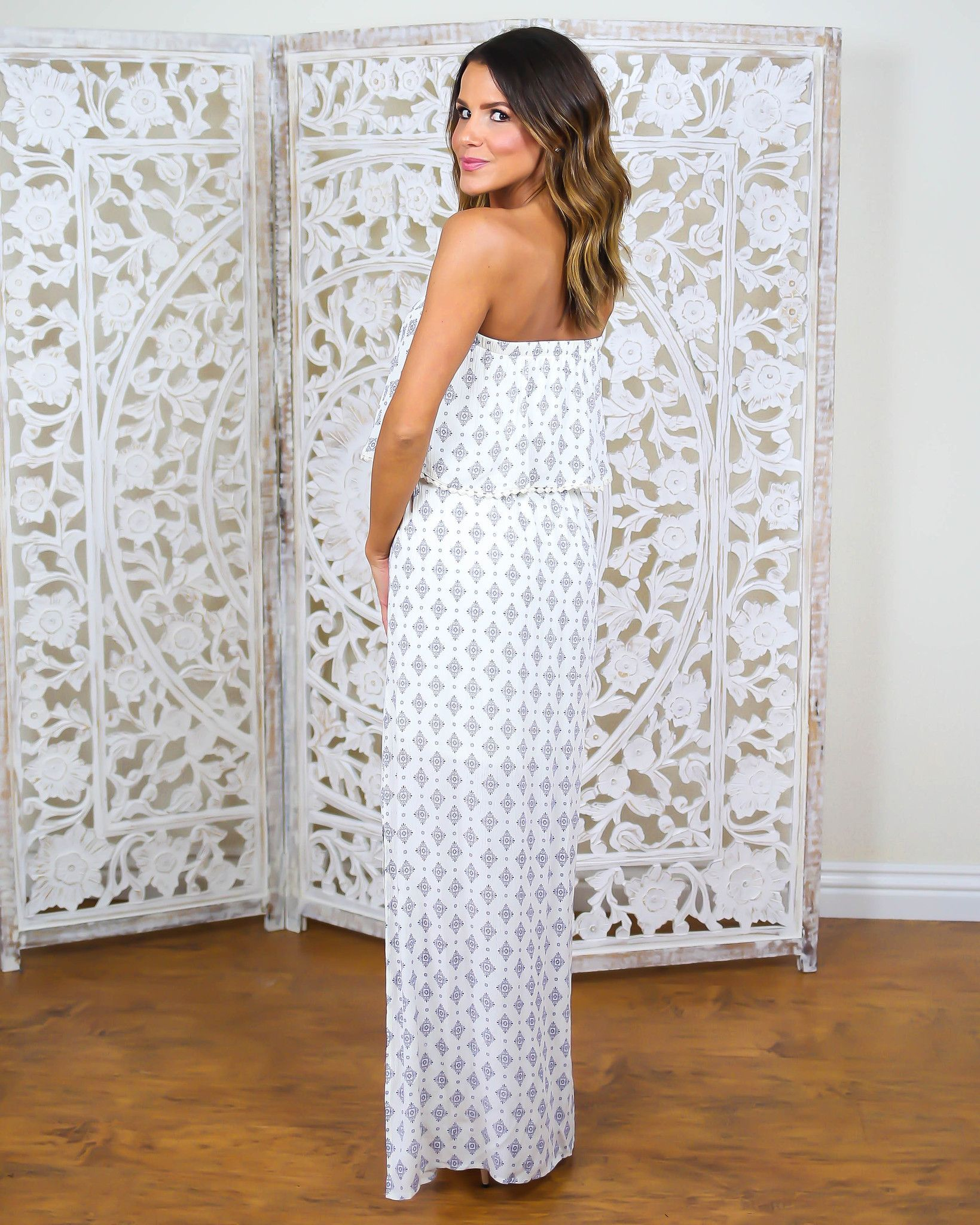 Our gorgeous Sunbent Maxi Dress is a stunning must have for Spring events. We love the stunning and simple silhouette with a cream and navy pattern that is boho and classic at the same time. The tiny medallion style pattern detail beautifully accents this strapless maxi dress, fully lined and finished with a subtle side slit. Tassel detailing on the shelf of this dress gives a weekend ready vibe.