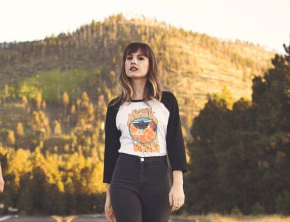 Inspired by mid-century rock n roll show posters and the desert landscape of the American Southwest, our logo was the first thing we ever put on a tee — because our customers kept asking us for it! — and now its available in mens/unisex sizes! The shirt is soft, thin, and lightweight, just like those favorites from the 70s and 80s. The desert-inspired artist-drawn logo is available in a variety of other Desert Child styles, but this black and white raglan is a best-selling favorite. There…