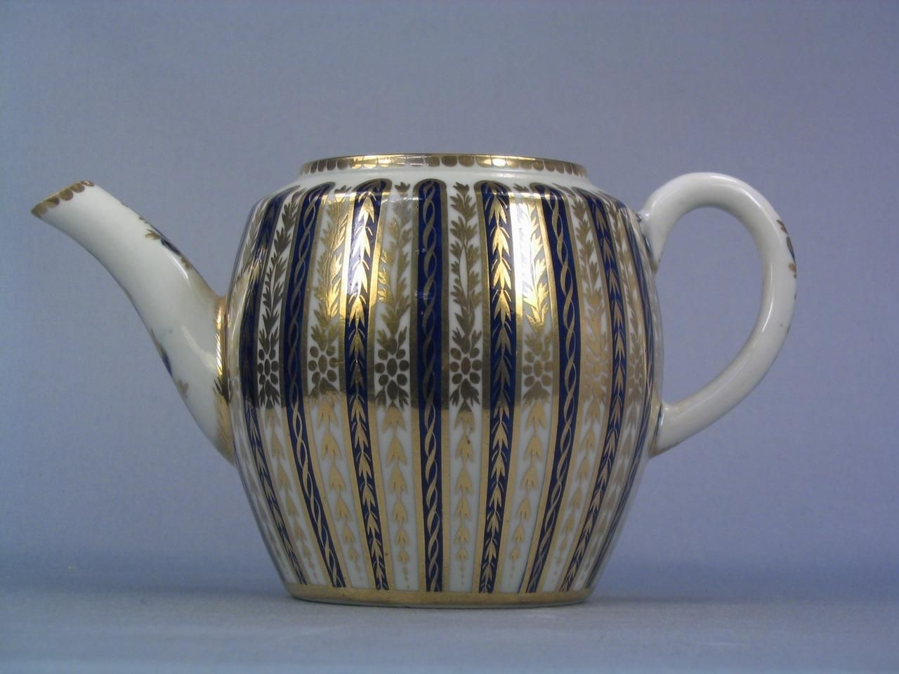 Worcester porcelain teapot; decorated with vertical stripes of mazarine blue and gilt leaves; gilt highlights  Materials: porcelain  Measurements: 82 (height)  Accession number: NWHCM : 1992.226.1516
