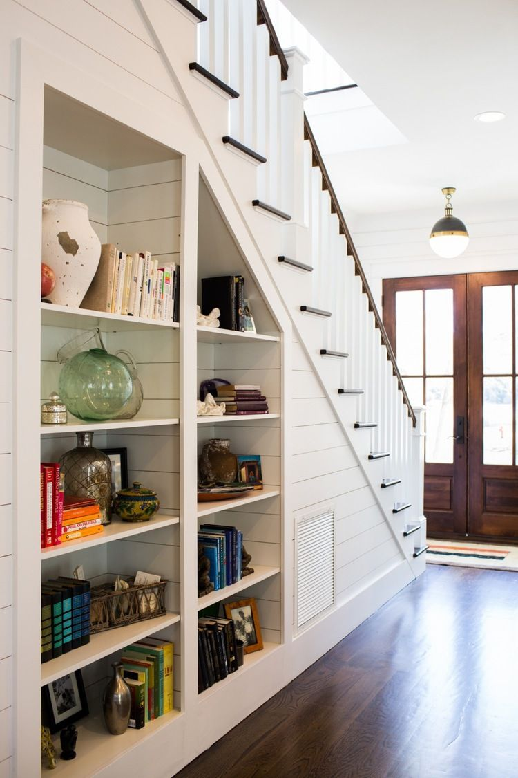 love the built in bookshelves under the staircase such a