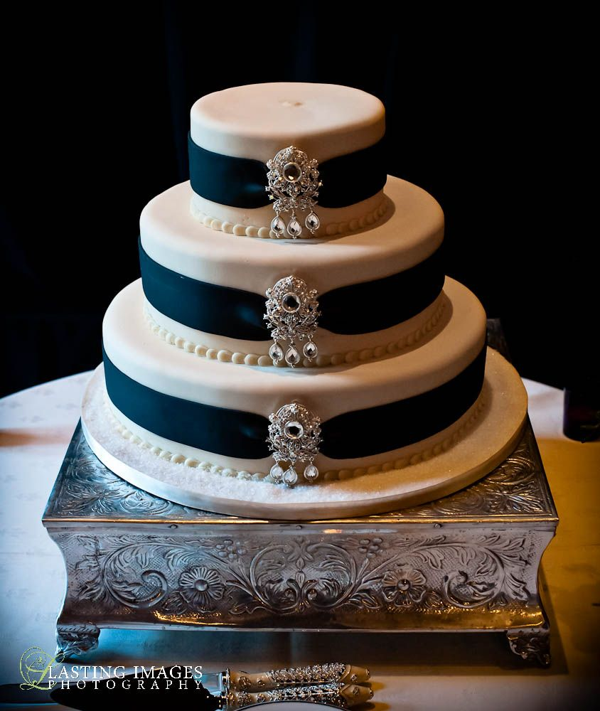 Three-tiered round white fondant cake with black ribbon and diamond and silver embellishments | Lasting Images photographt | villasiena.cc