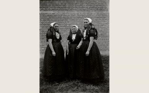 Drie vrouwen in Axelse streekdrachtDrie vrouwen in Axelse streekdracht. Ze zijn gekleed in opknapdracht en dragen over de ondermuts en het oorijzer een 'trekmuts'. Een opvallend onderdeel van de Axelse vrouwendracht is de hoog opgespelde schouderdoek, die met papier verstevigd wordt. 1918-1941 vanAgtmaal #Zeeland #Axel