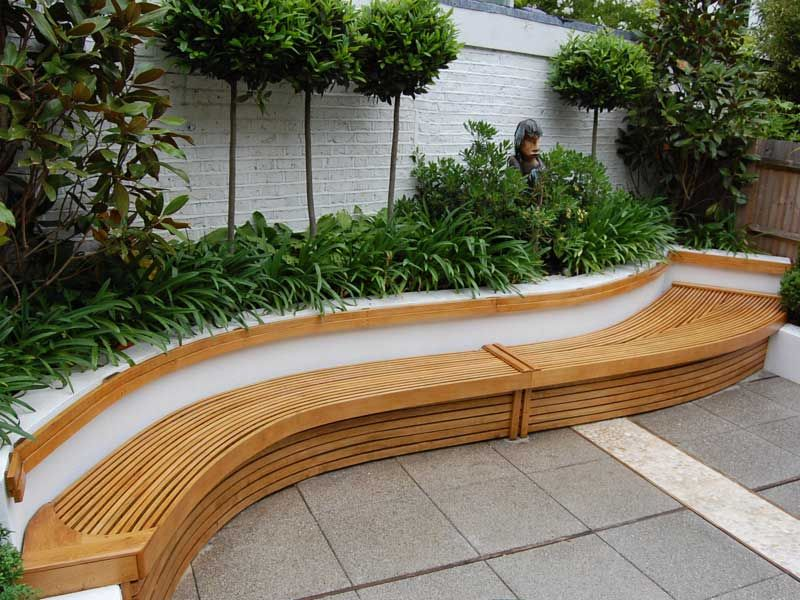 lovely curved wall seat with wood trim and planted border