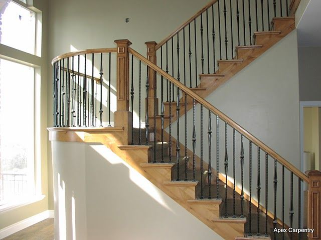A curved stair rail with metal balusters built in the Salt Lake area.