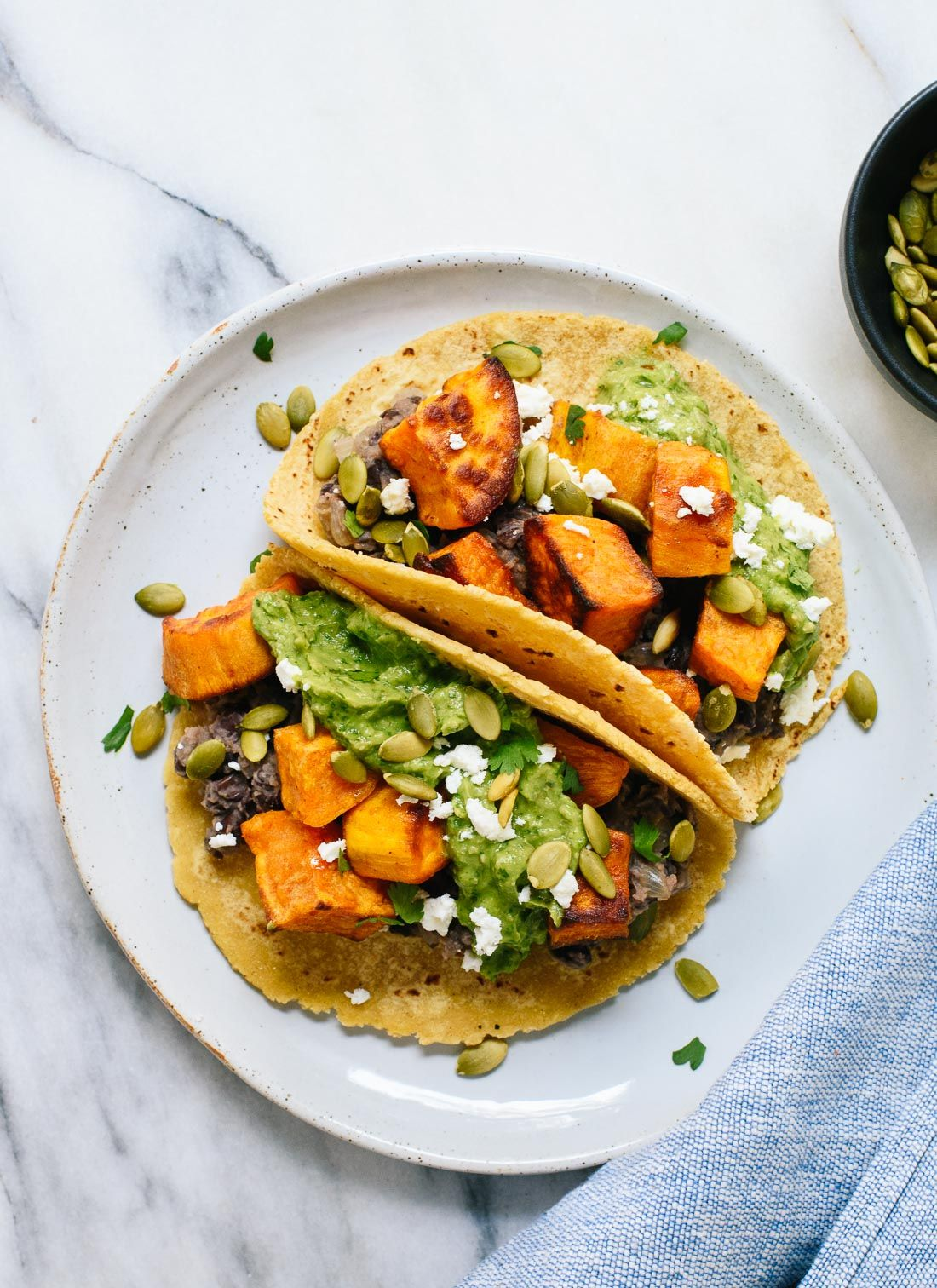 These roasted sweet potato tacos feature spicy black beans and avocado-pepita dip. Delicious! This taco recipe is vegetarian (easily vegan) and gluten-free.