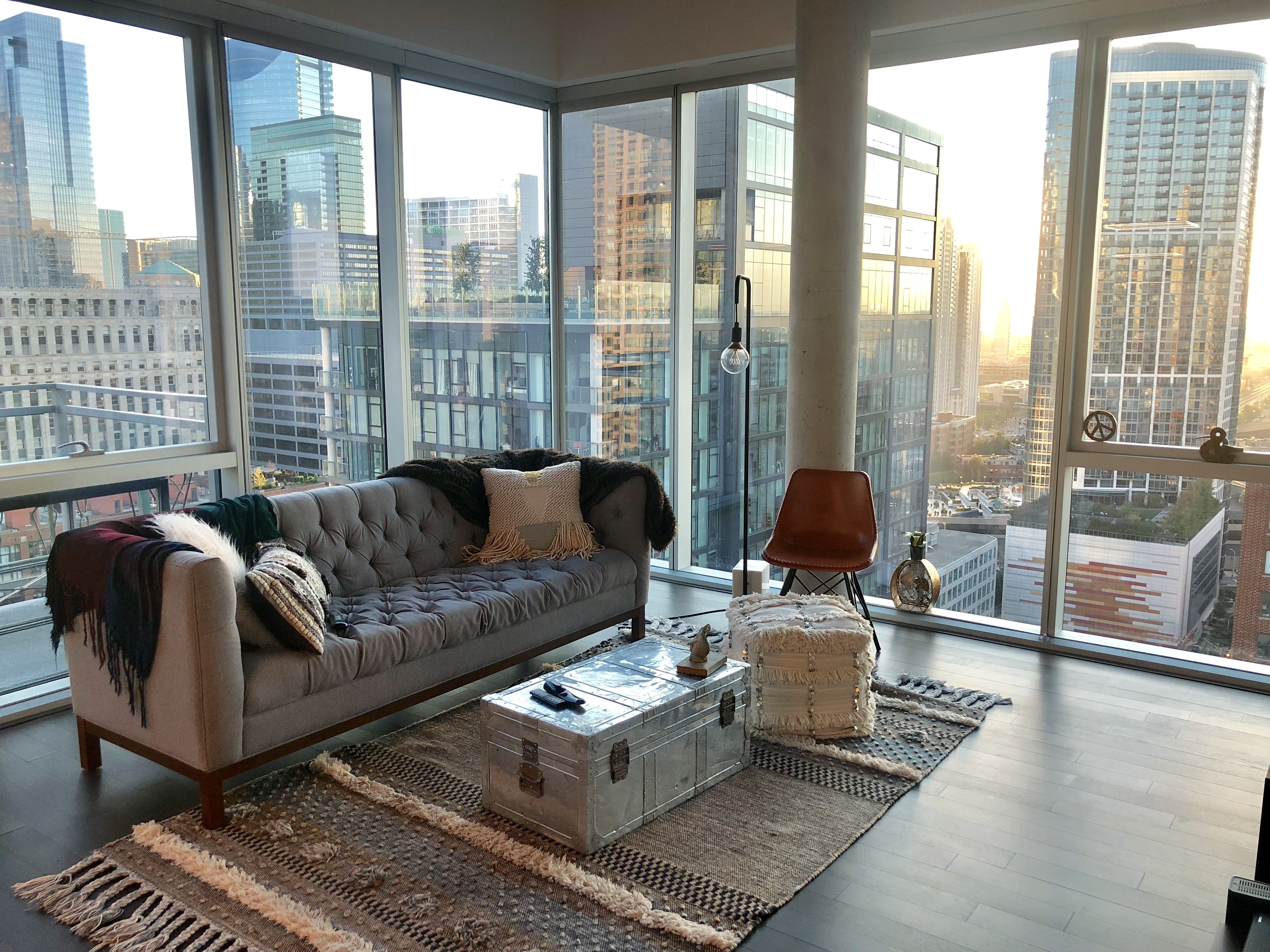 Modern Living Room With Floor To Ceiling Windows Hardwood Floors Concrete Ceilings Grey Suede C City Apartment Decor Apartment Living Room Chicago Apartment