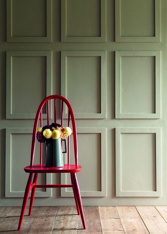 chaise rose flashy et mur vert kaki