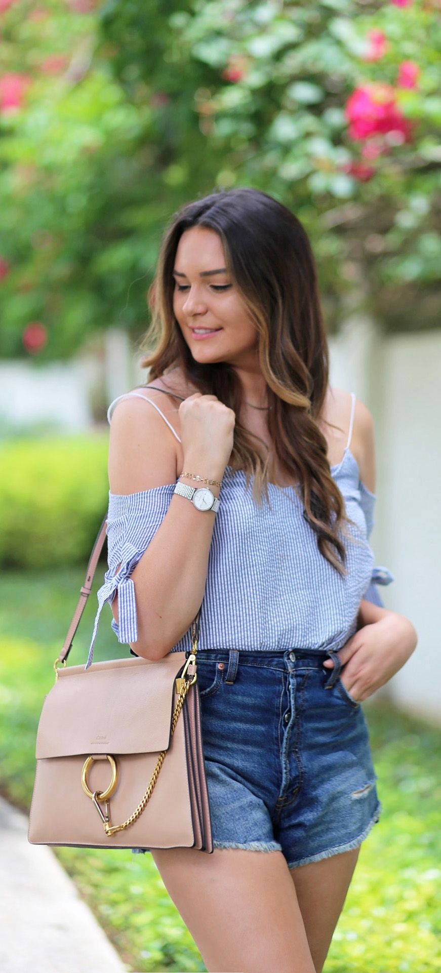 3f55f001340 Fashion blogger Mash Elle styles a blue striped seersucker off the shoulder  top with high waisted cut off ripped jeans short and @mauricelacroix watch.  #ad