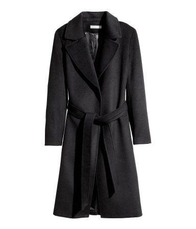 Let figursyet frakke i filtet uldblanding. Den har bindebælte i taljen og lommer i sidesømmen. Frakken er uden lukning og har slids bagpå. Foret.