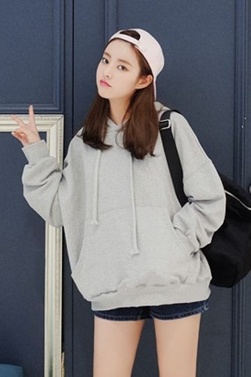 pink cap , large over sized white pullover hoodie , dark denim shorts ,  black backpack